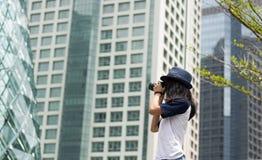 La muchacha asiática toma la foto en ciudad Fotos de archivo libres de regalías