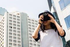 La muchacha asiática toma la foto en ciudad Imagenes de archivo