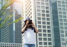 La muchacha asiática toma la foto en ciudad Foto de archivo libre de regalías