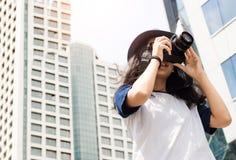 La muchacha asiática toma la foto en ciudad Foto de archivo