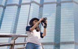 La muchacha asiática toma la foto en ciudad Fotografía de archivo libre de regalías