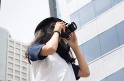 La muchacha asiática toma la foto en ciudad Imagen de archivo