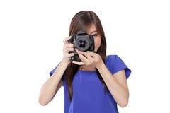La muchacha asiática toma una imagen con la cámara digital Fotos de archivo libres de regalías