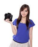 La muchacha asiática trae una cámara digital Imagenes de archivo