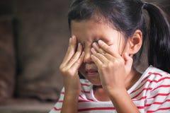 La muchacha asiática triste del niño es gritadora y de frotamiento de ella los ojos fotos de archivo