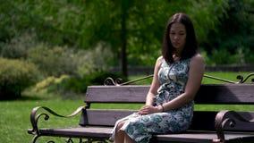 La muchacha asiática triste se está sentando en el banco en el parque Rasgones que ruedan abajo la mejilla almacen de video
