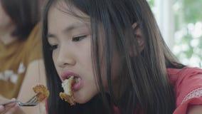 La muchacha asi?tica del ni?o est? comiendo el desayuno por la bifurcaci?n metrajes