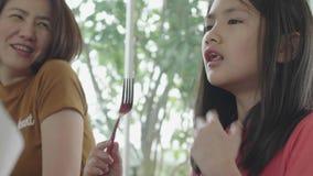 La muchacha asi?tica del ni?o est? comiendo el desayuno por la bifurcaci?n almacen de metraje de vídeo
