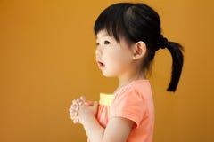 La muchacha asiática del niño del bebé está rogando Fotografía de archivo libre de regalías