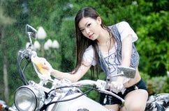 La muchacha asiática hermosa está lavando la bici grande Fotografía de archivo libre de regalías