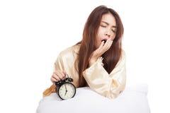 La muchacha asiática soñolienta despierta con la almohada y el despertador Fotografía de archivo