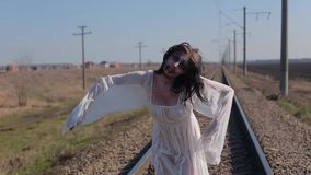La muchacha asombrosa en el vestido translúcido blanco y con maquillaje de la cera en cara en forma de herida sangrienta hace dan metrajes