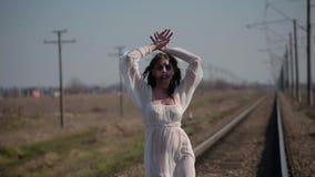 La muchacha asombrosa en el vestido translúcido blanco y con maquillaje de la cera en cara en forma de herida sangrienta hace dan almacen de metraje de vídeo