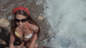 La muchacha asombrosa en un bikini coloreado brillante es metrajes
