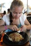 La muchacha asperja los espaguetis con queso Imagenes de archivo