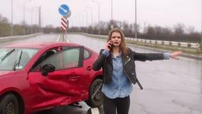 La muchacha asustada que habla en el tel?fono despu?s de un accidente de tr?fico bajo la lluvia, coche est? quebrada almacen de video