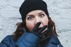La muchacha asustada rizado-cabelluda en un sombrero negro hace un selfie, foto de la calle fotos de archivo