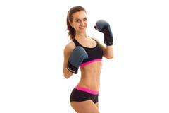 La muchacha atlética atractiva sonriente sonríe llevando a cabo las manos en guantes de boxeo Imágenes de archivo libres de regalías