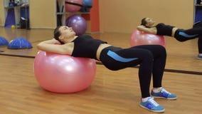 La muchacha atlética balancea la prensa en fitball en gimnasio almacen de metraje de vídeo