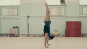 La muchacha atlética, en el gimnasio, sube en sus brazos, paseos hacia la cámara, mientras que gira alrededor de su eje almacen de video