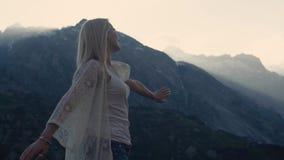 La muchacha atlética está bailando en el top del mundo, de las montañas hermosas y del cielo azul en el horizonte Ella está inten