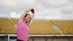 La muchacha atlética estira sus brazos y detrás antes de correr metrajes