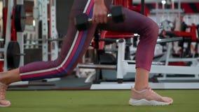 La muchacha atlética hermosa de la aptitud en ropa de deportes está haciendo ejercicios delanteros de la estocada en el gimnasio almacen de video