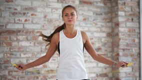 La muchacha atlética joven es cuerda de salto en el fondo de la pared de ladrillo almacen de video