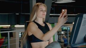 La muchacha atlética joven es que se sienta y que habla con la familia por la cámara del smartphone almacen de metraje de vídeo