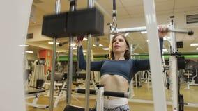 La muchacha atlética joven sacude su detrás y las manos en el gimnasio usando un simulador almacen de metraje de vídeo