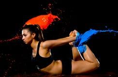 La muchacha atlética joven se bañó en la pintura azul que hacía detrás estirar ejercicio Imagenes de archivo