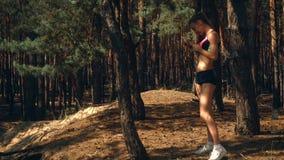 La muchacha atlética linda se coloca cerca de un árbol en el bosque y los controles en su mano llaman por teléfono almacen de metraje de vídeo