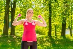 La muchacha atlética mantiene forma durante embarazo foto de archivo