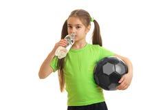 La muchacha atlética menuda que sostiene una bola y la bebida riegan de una botella Foto de archivo libre de regalías