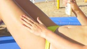 La muchacha atractiva aplica la protección solar para las piernas HD metrajes