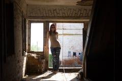 La muchacha atractiva atractiva de moda joven en vidrios y vaqueros coloca el interior un edificio destruido en el mediodía solea Imagen de archivo