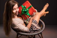 La muchacha atractiva atractiva sensual se sienta en una silla con Fotografía de archivo