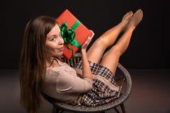 La muchacha atractiva atractiva sensual se sienta en una silla con Imagen de archivo libre de regalías