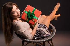La muchacha atractiva atractiva sensual se sienta en una silla con Imagenes de archivo