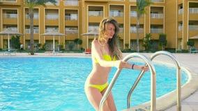 La muchacha atractiva camina en la piscina HD metrajes