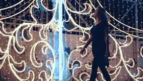 La muchacha atractiva camina a través de la ciudad en la Navidad en crecimiento completo almacen de video