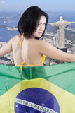 La muchacha atractiva celebra la bandera del Brasil en la ciudad Foto de archivo libre de regalías