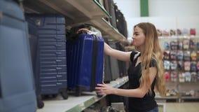 La muchacha atractiva compra equipaje almacen de video