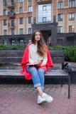 La muchacha atractiva con el pelo largo se sienta en un banco, cubierto en una manta roja, en un nuevo cuarto residencial y le es Imagen de archivo