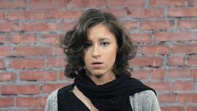 La muchacha atractiva con el pelo rizado representa tristeza in camera bastidor Pared de ladrillo almacen de metraje de vídeo