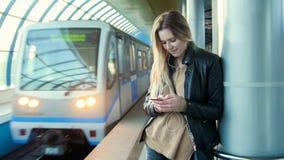 La muchacha atractiva con el pelo rubio largo del artilugio en la chaqueta de cuero endereza la situación en metro contra la pers Imagenes de archivo