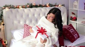 La muchacha atractiva con el regalo de Navidad se sienta en la cama almacen de metraje de vídeo