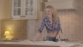 La muchacha atractiva con un cuerpo sensual está preparando la pasta mientras que se coloca en la tabla de cocina La muchacha ale almacen de video
