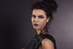 La muchacha atractiva creativa en un chaleco negro mira Fotos de archivo libres de regalías