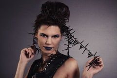 La muchacha atractiva creativa en un chaleco negro mira Foto de archivo libre de regalías